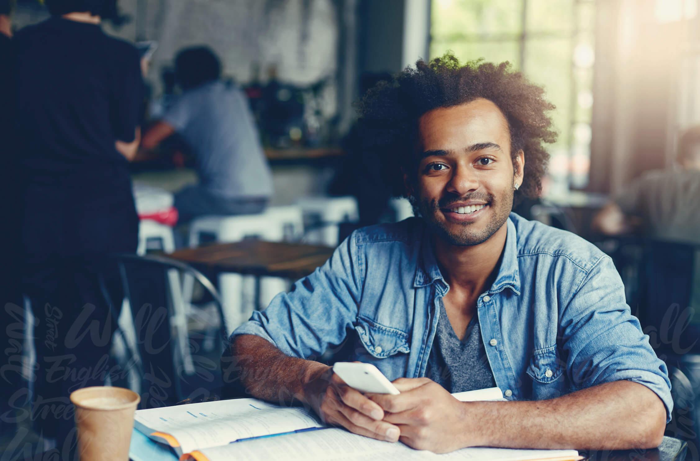 chico joven estudiando los tiempos verbales en ingles con un movil en la mano y un libro en un cafeteria